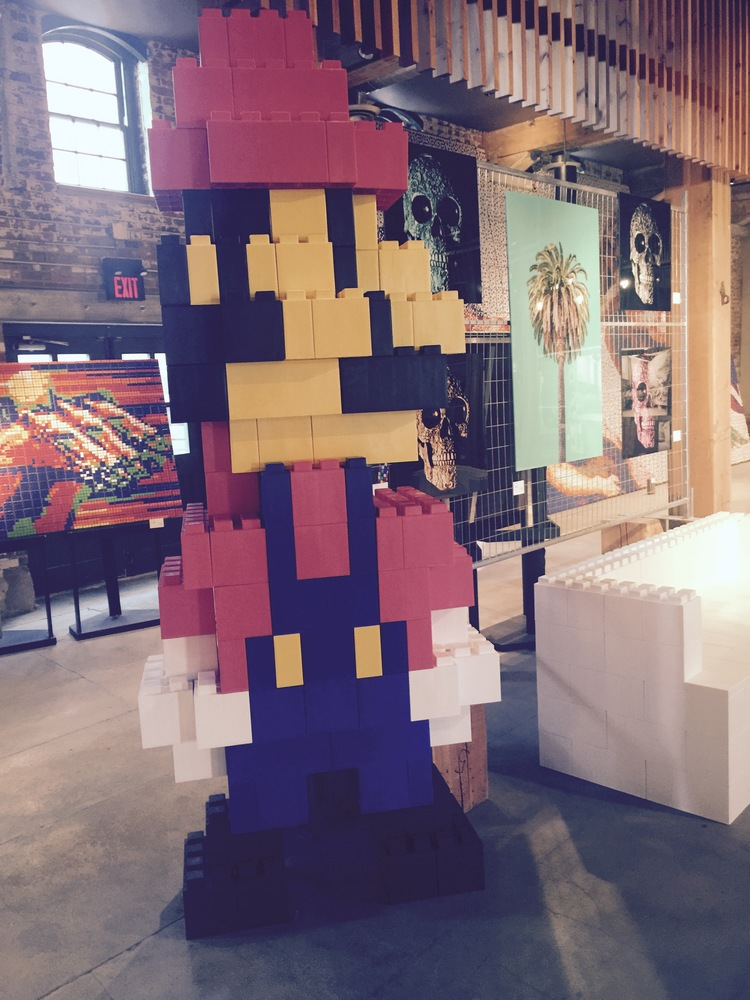 A giant Mario statue made of EverBlocks that look like life-size LEGO bricks.