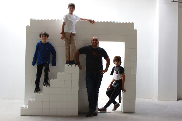 EverBlock Systems Founder and CEO Arnon Rosan is standing with his three sons in front of a white wall made of EverBlocks.