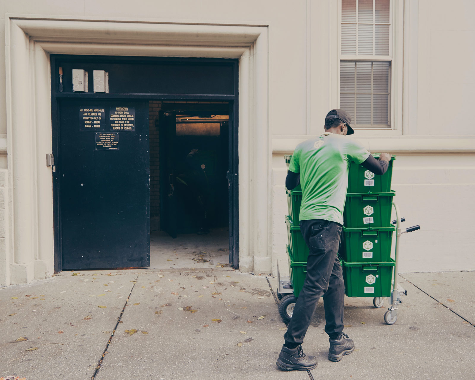 Darrell Green, a MakeSpace Uploader, father, and veteran is wheeling MakeSpace storage bins outside of a building in NYC.