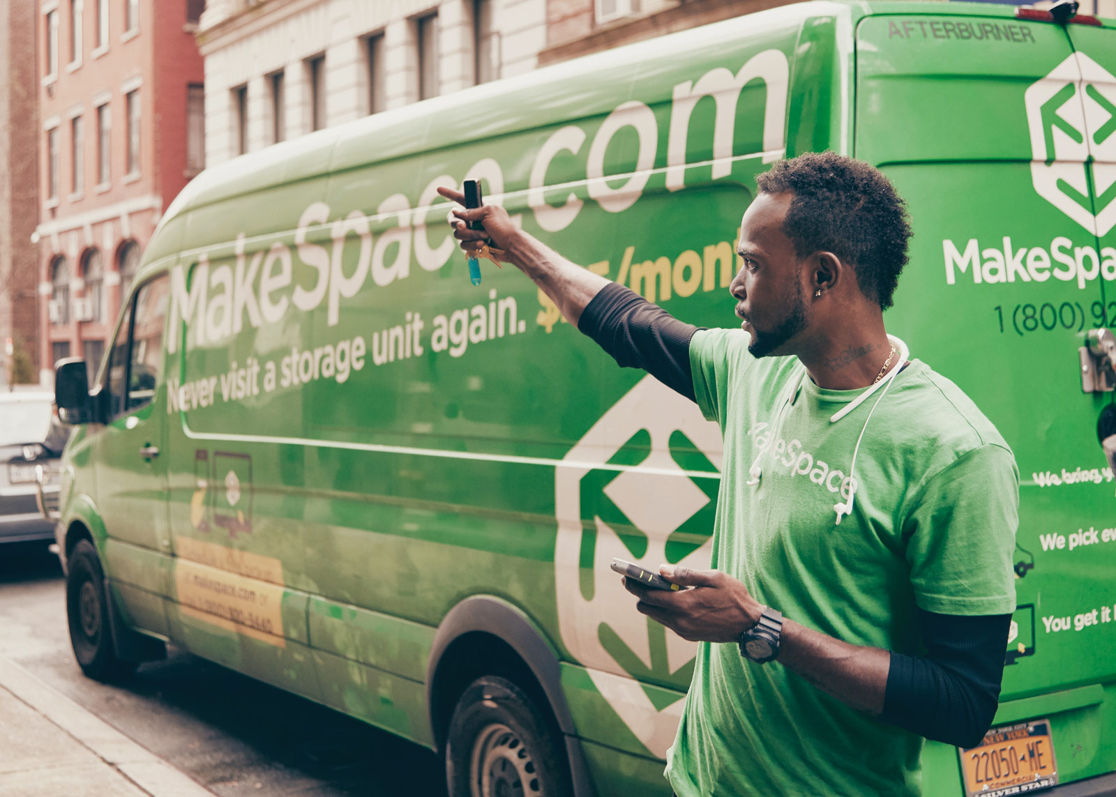 Darrell Green, MakeSpace Uploader, father, and veteran, is standing to the side of a MakeSpace van and pointing up in the air.