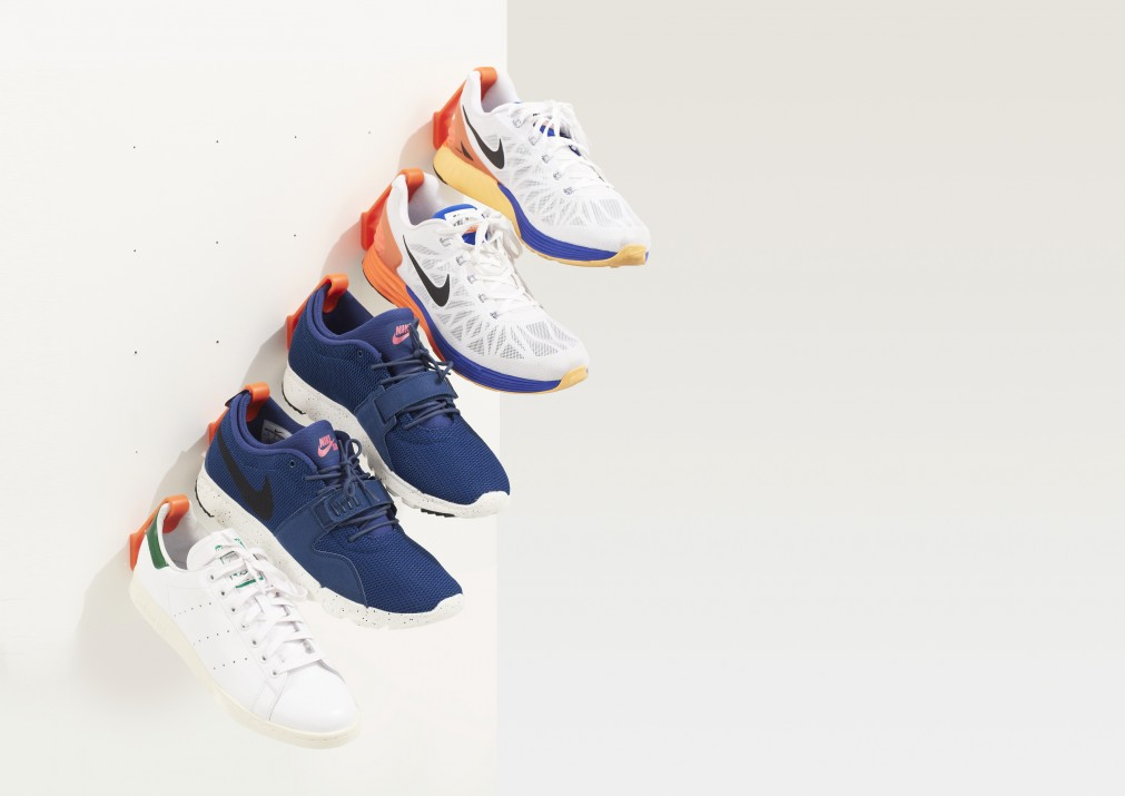 5 orange Staeckler shoe storage hooks are mounted diagonally to a white wall and hanging 5 sneakers.
