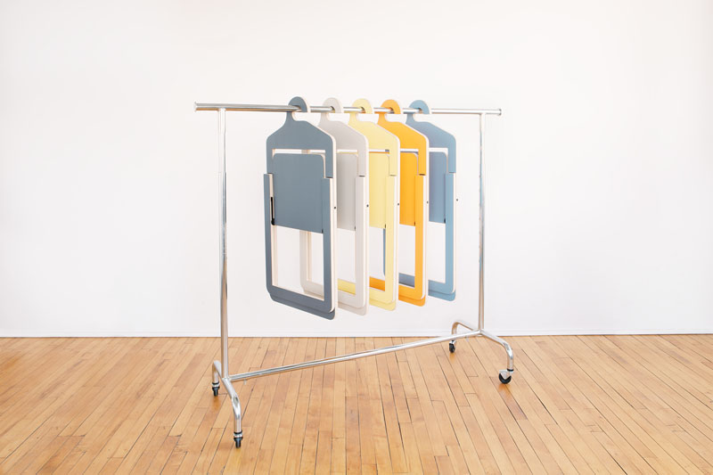 Black, grey, yellow, coral, and marine Umbra Shift Hanger Chairs are hanging on a rolling clothes rack.