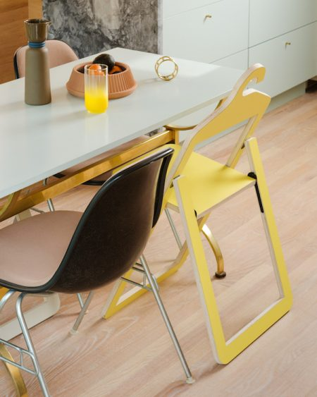 umbra shift yellow hanger chair next to a black chair at a thin white dining table in an apartment kitchen