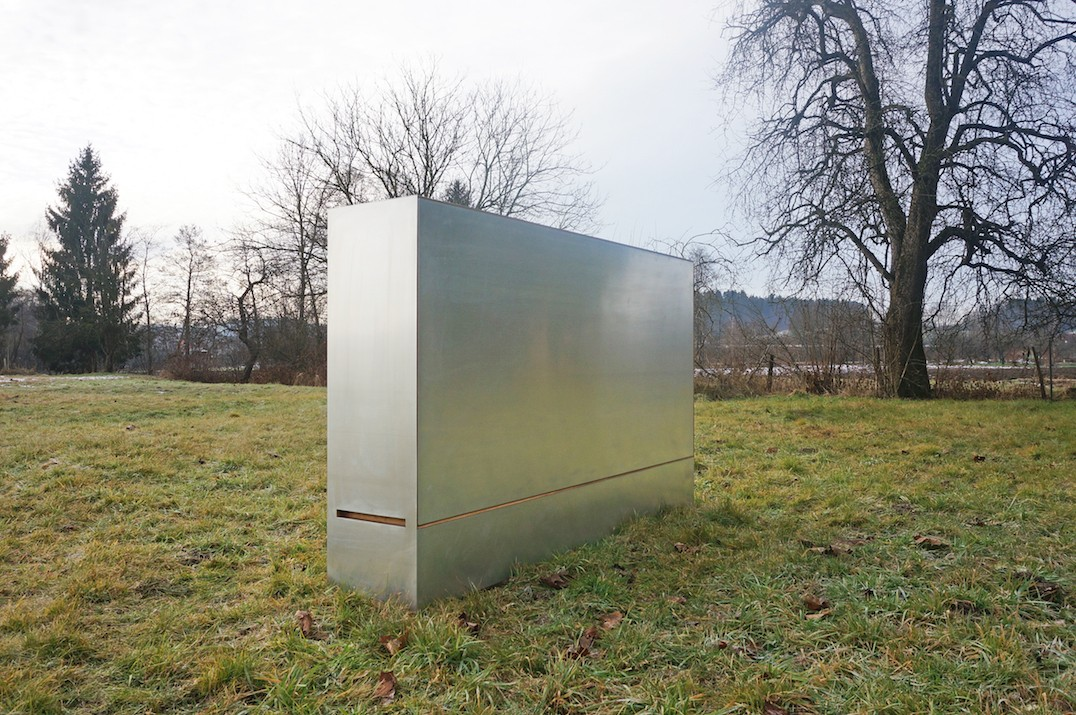 A closed Travelbox, a portable room in a box by JUUST Design, is standing in the grass.