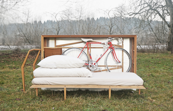 JUUST Design's Travelbox is standing in the grass and open, showing a mattress, table, chair, bike, and pillows in storage.