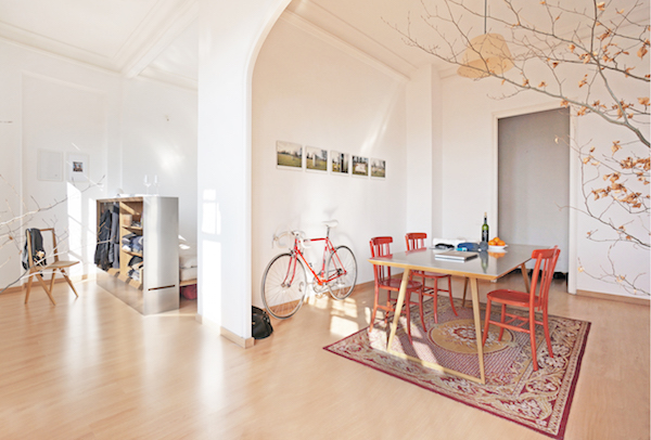 Travelbox is inside of a clean, minimally-decorated tiny apartment, storing clothes, and surrounded by a chair, bike, dining table, and chairs.