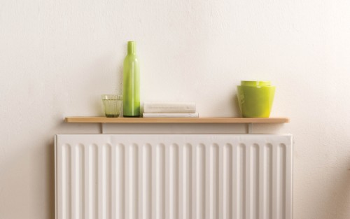 A drinking glass, decorative vase, books, and pots are stored on top of a radiator shelf kit from B!Organised.