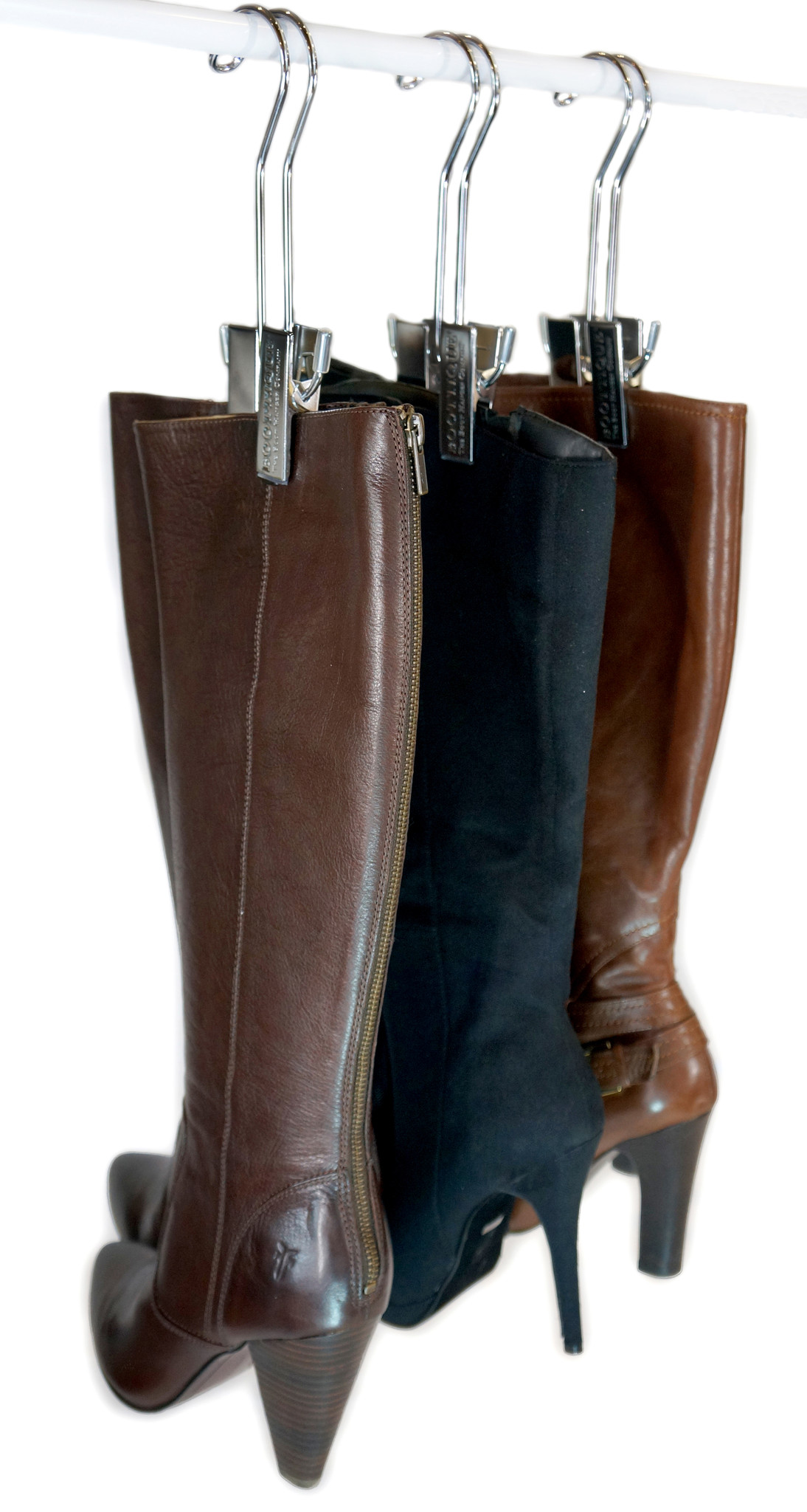 3 silver Bootique Boot Hangers are organizing 2 brown boots and 1 black boot on a closet rod.