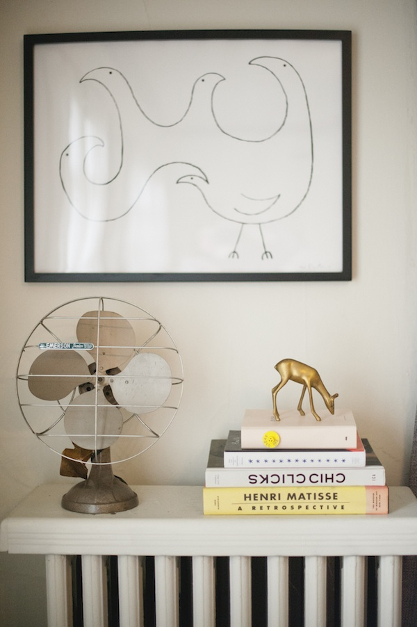 A white radiator shelf is storing an old metal fan, four stacked books, and a brass deer figurine on top.