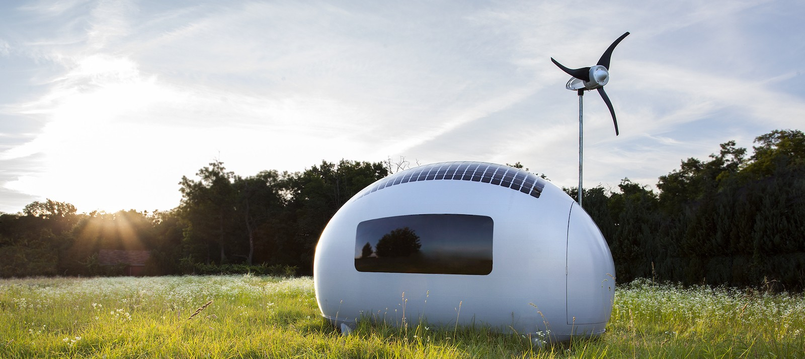 The Ecocapsule, a self-sufficient pod/tiny house on wheels that's available for pre-order, is outside in the grass during the daytime.