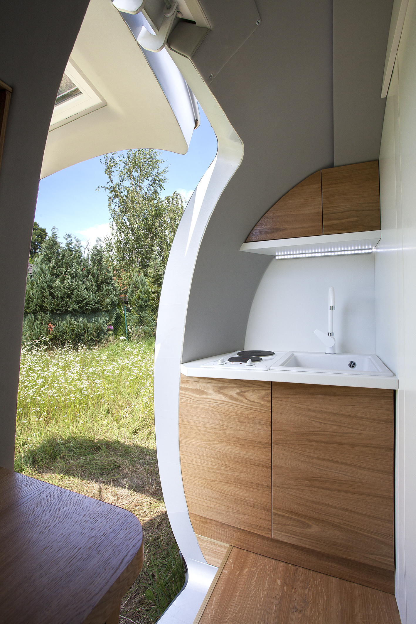 The Ecocapsule's kitchenette with a sink, two burners, and storage cabinets.