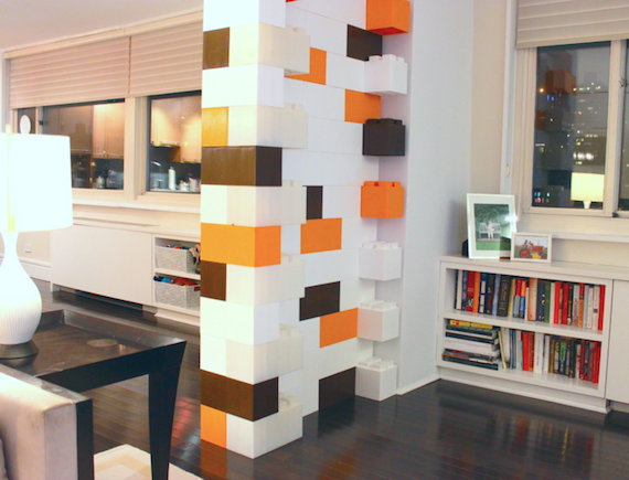 The interior of a small apartment with a room divider/accent wall made of EverBlocks that resemble giant LEGOs.