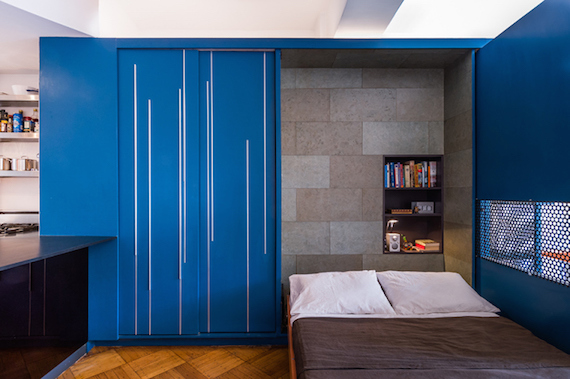 The bedroom, murphy bed, mattress, pillows, bookshelf, and closet inside of Unfolding Apartment's blue storage cabinet/transforming furniture.