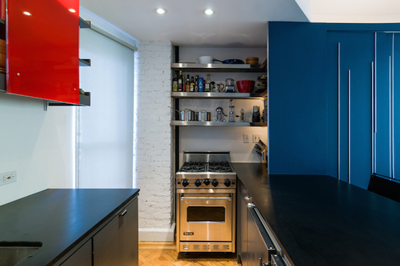 The kitchen inside of Unfolding Apartment, a tiny studio in Manhattan NYC that has a big blue piece of multipurpose furniture with storage.