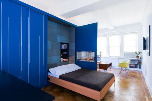 The interior of the Unfolding Apartment in Manhattan, New York has a blue convenient self-storage unit with a murphy bed, home bar, closet, and more.