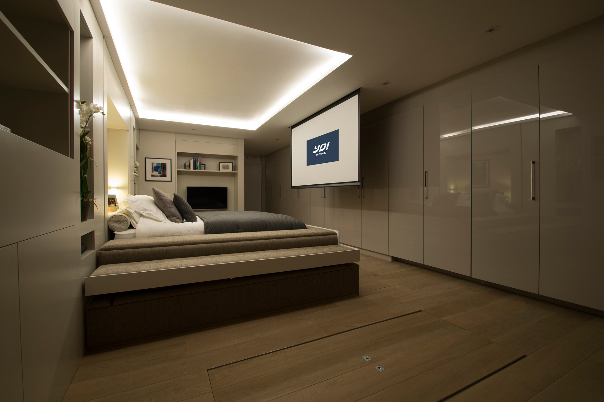 YO! Home's projector screen is hanging from the ceiling and it's motorized bed rests on a sunken U-shaped sofa.