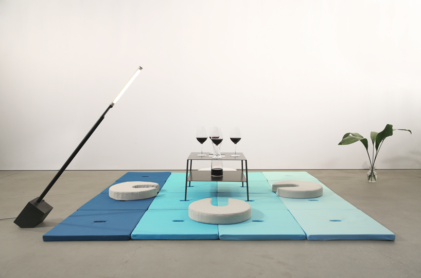 Square Pile cushions form tatami flooring, four circular Pile cushions form seats, and a metal table is storing four wine glasses and a carafe.