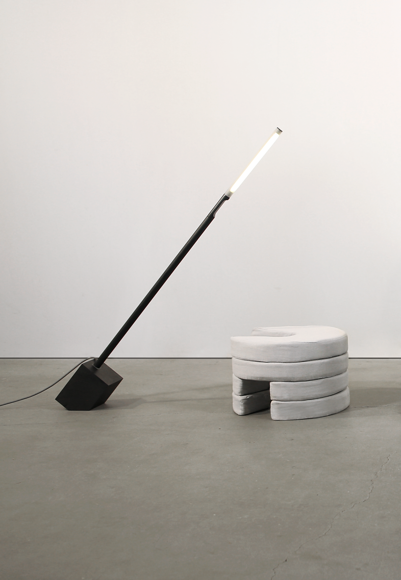 A thin black floor lamp is leaning over a seat made of circular Pile foam cushions.