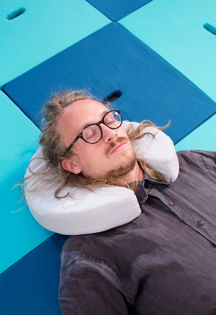 A man with glasses and long blonde hair is wearing a circular Pile cushion as a neck pillow and lying on a bed made of square Pile pieces.