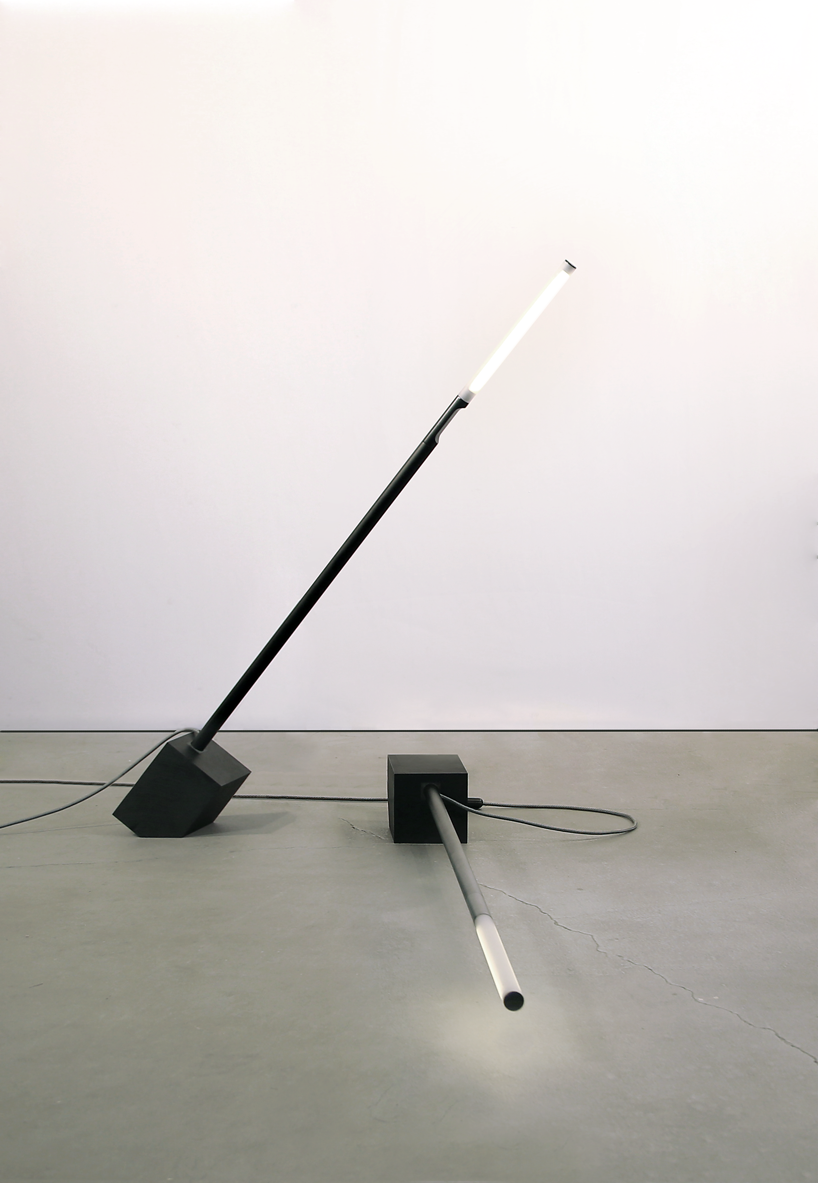 A skinny black Pile floor lamp is leaning over another floor lamp that's sleeping on the floor.