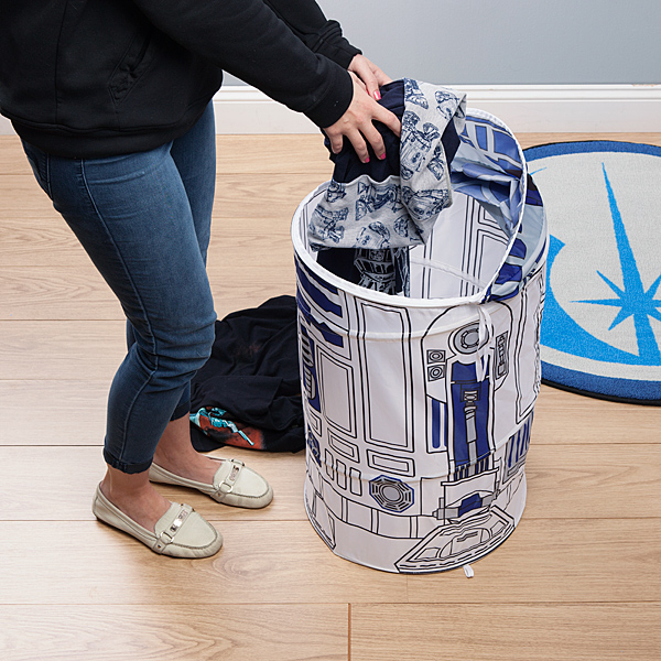 A woman is putting clothes into a collapsible Star Wars R2-D2 laundry hamper/storage bin.