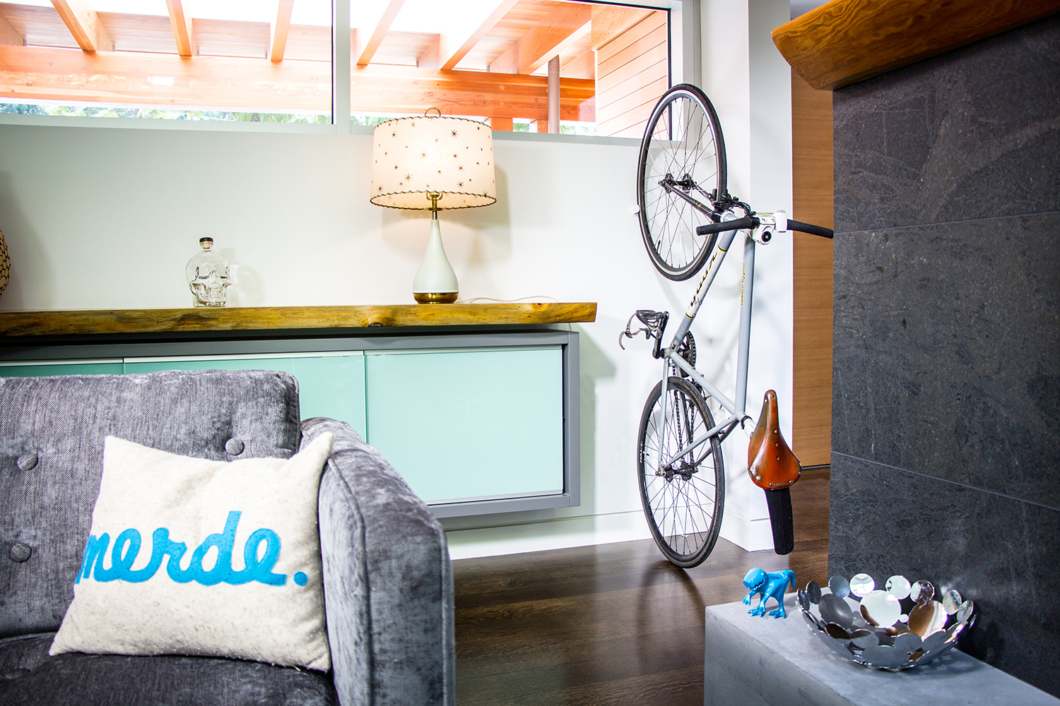 A white CLUG, which is a bike storage clip that mounts to a wall, is storing a bicycle upright in a small apartment.