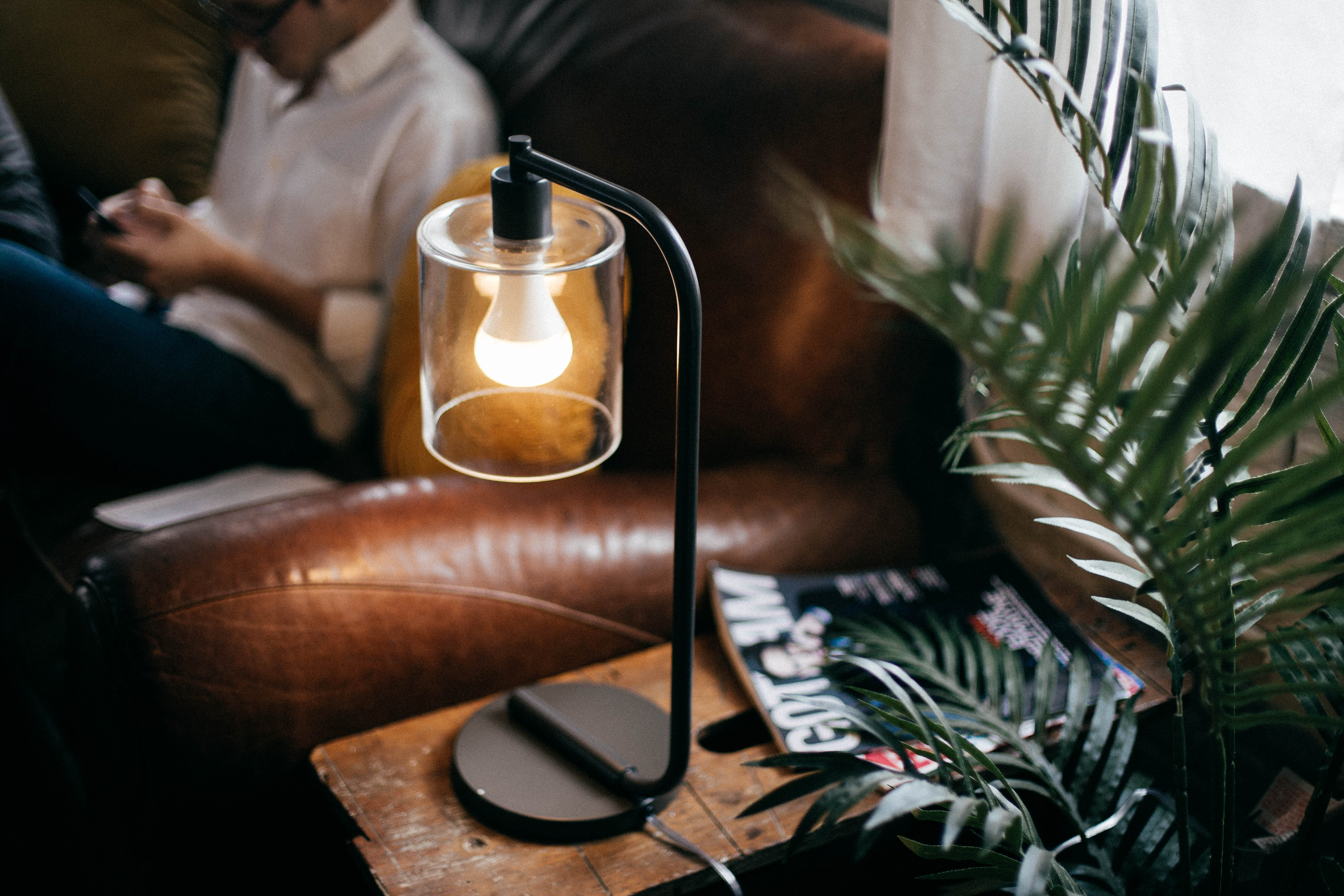 A space-saving Twist Smart LED Lightbulb, which is also an AirPlay speaker, is installed in a tiny black lamp and glowing.