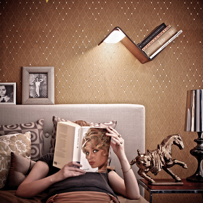 A LiliLite, which is a wooden bookshelf, bookmark, and lamp that mounts to a wall, is shining over a woman reading a book in bed.