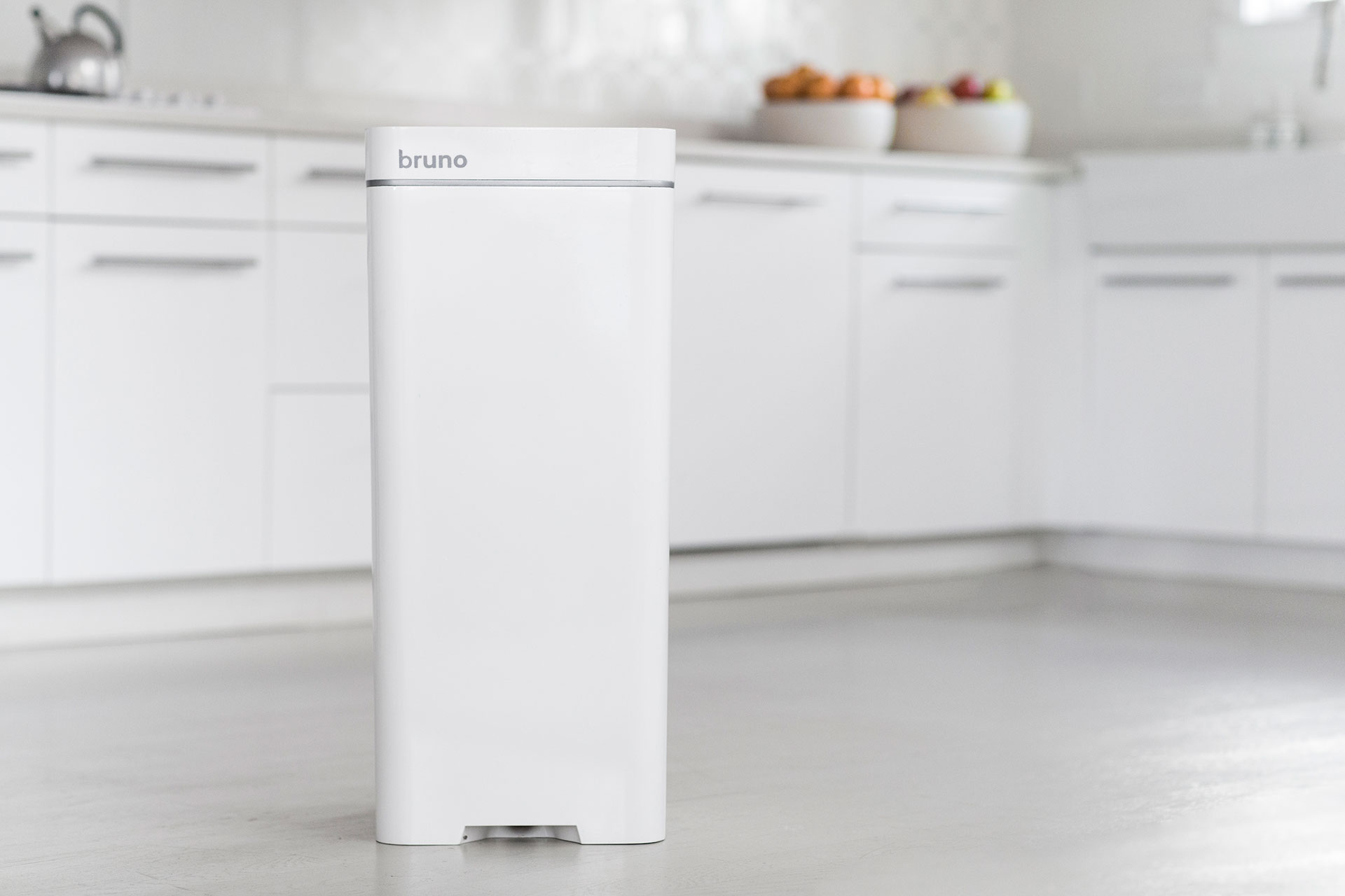 A white BrunoSMART trashcan/vacuum is inside of a white kitchen in a tiny apartment.
