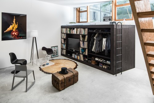 A black Living Cube, which is a piece of wooden space-saving furniture that has a storage unit, is in the corner of a stylish living room.