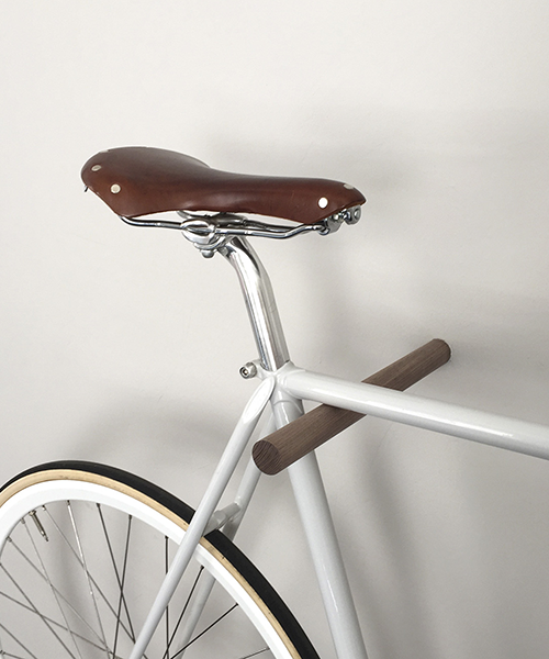A brown fluo wooden bike hook is mounted to a white wall and hanging a white bicycle with a brown leather seat.