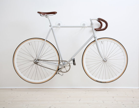 White Alexa Lethen Bike Hooks are mounted on a wall and storing a white bicycle in the air in a small apartment.