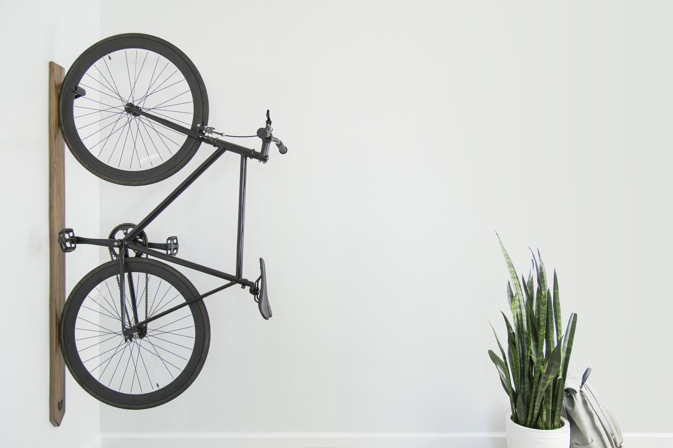 An Artifox Black Walnut Rack is mounted to a white wall in a tiny apartment and storing a black bike vertically.