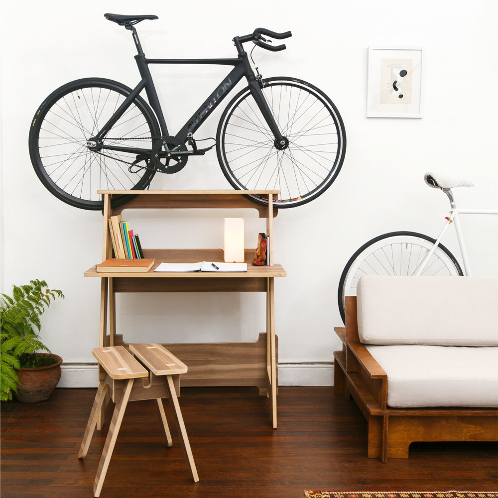 A wooden Chol1 DE5K bike storage desk is on hardwood floor in a clean tiny apartment and storing a black bike.