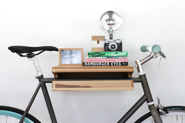 A Knife & Saw white oak Bike Shelf is mounted to a white wall and storing a black bike, books, a framed picture, fake teeth, and a vintage camera.