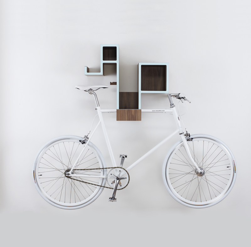 A veneer Tamasine Osher Pedal Pod is mounted to a light gray wall and storing a white classic bicycle.