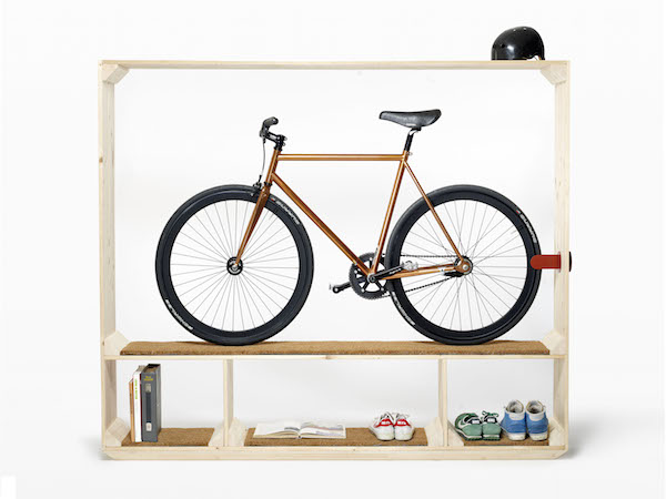 A wooden Post Fossil Shoes, Books and a Bike is storing an orange road bike, a black bicycle helment, and multiple shoes and books on shelves.