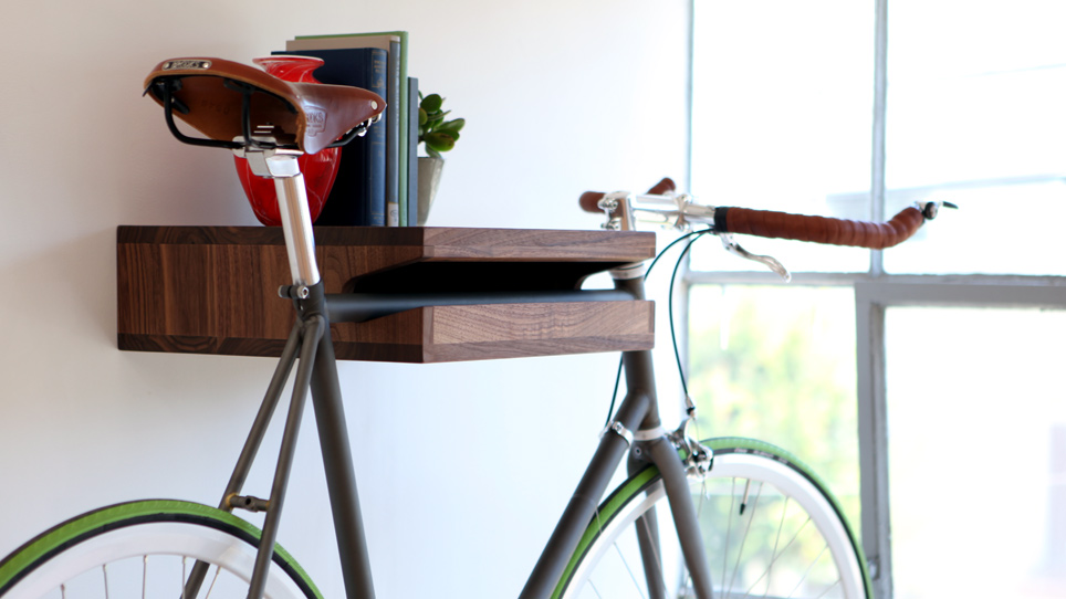 A walnut Knife & Saw Bike Shelf is storing a bicycle, red vase, four books, and a small plant.