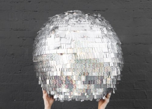 2 hands are holding up a DIY NYE disco ball pinata in front of a dark gray brick wall.