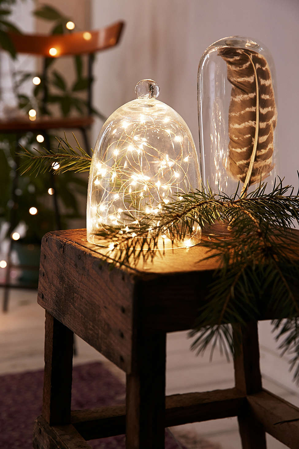 A terrarium is storing glowing holiday decoration string lights on a wooden table in a small apartment.
