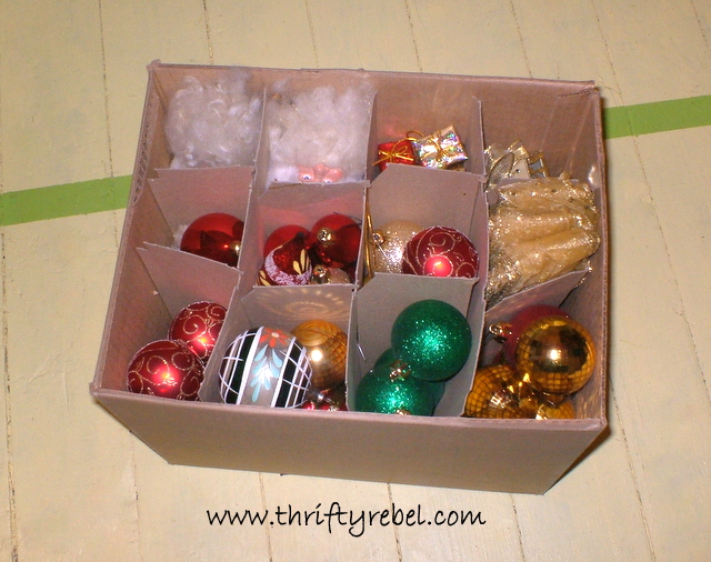 A Christmas ornament holiday decoration storage hack of various ornaments in a wine box from a liquor store.