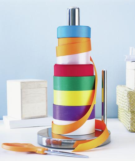 8 spools of colored ribbon stored on a paper towel stand is a cool holiday storage hack.