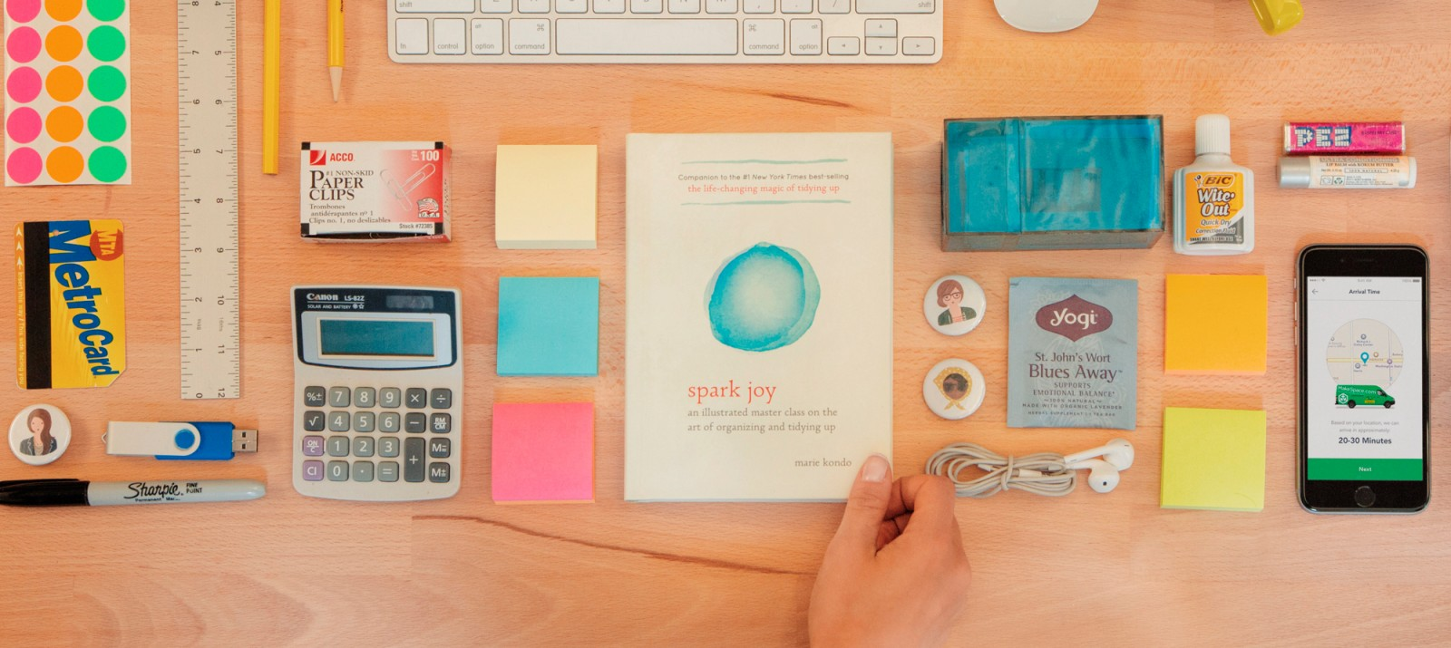 Marie Kondo's new book Spark Joy is on a desk that's organized neatly.