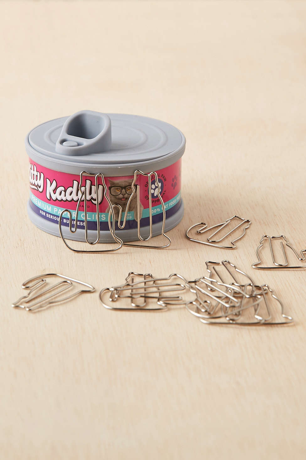 A Kitty Kaddy cat food can that stores paper clips.