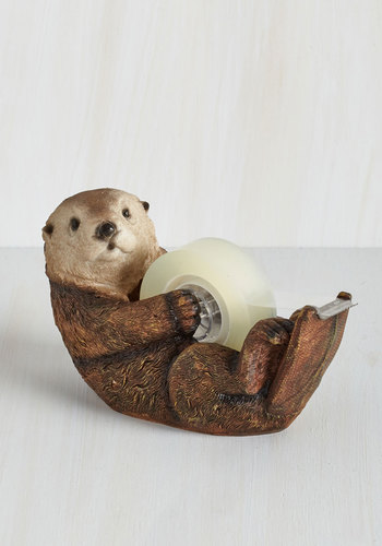 An otter tape dispenser is laying on a desk.
