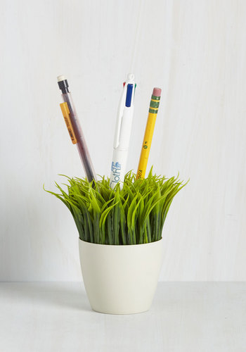 An Ideas in Bloom Desk Organizer from ModCloth that looks like grass storing pencils and a pen.
