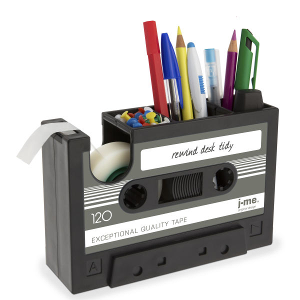 A Rewind Desk tidy, which looks like a black cassette tape, is storing pens, thumbtacks, pencils, and tape.