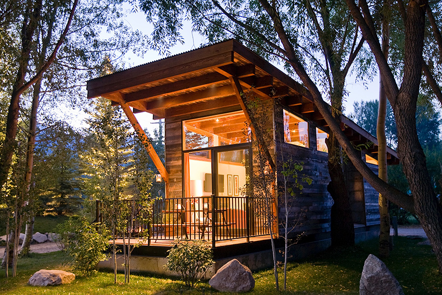 The Exterior Of A Wheelhaus Wedge Cabin In The Woods At Night.