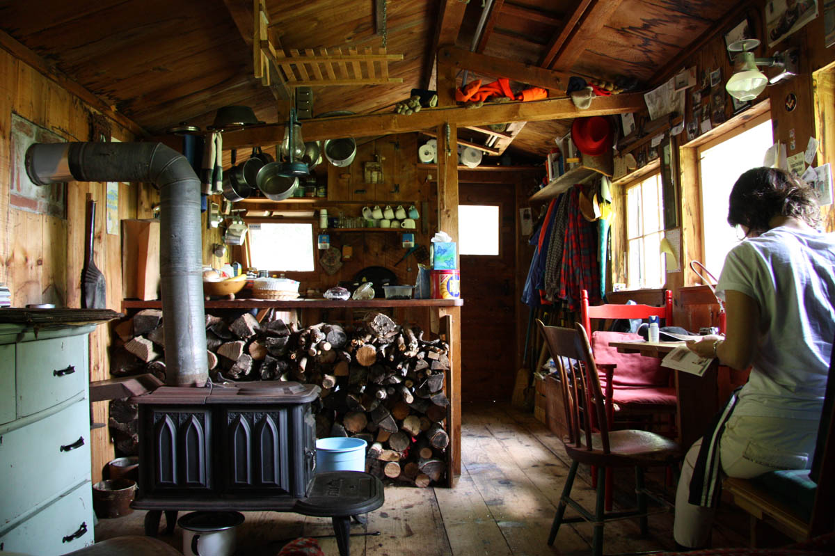 A woman is reading at a table in a minimally decorated cabin with a wood burner stove.