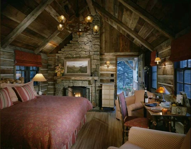 The cozy interior of a log cabin is dimly lit and minimally decorated.